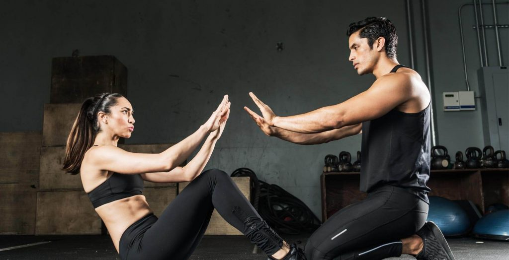 Personal trainer and client exercising