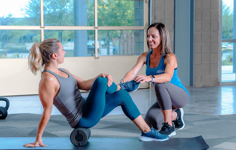 a personal trainer showing a client how to do foam rolling