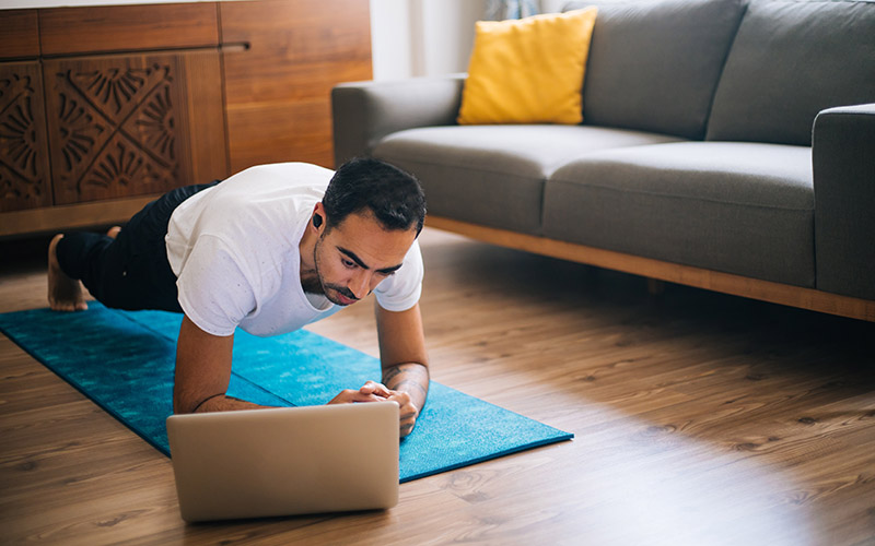man doing a plank in front of laptop